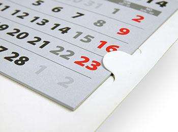 Kalendaria są przytrzymywane przez skrzydełka znajdujące się na plecach kalendarza trójdzielnego.